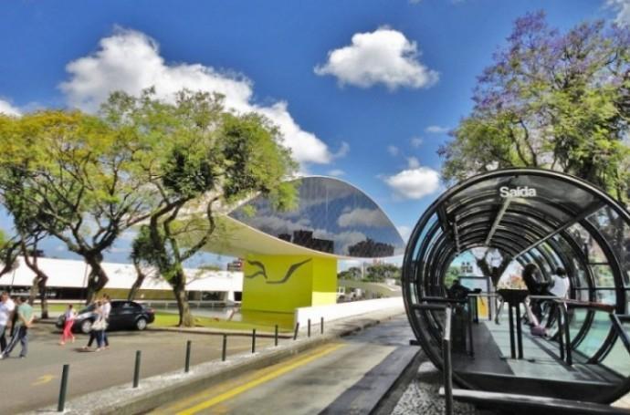 Tubo de transporte público em Curitiba com o MON ao fundo