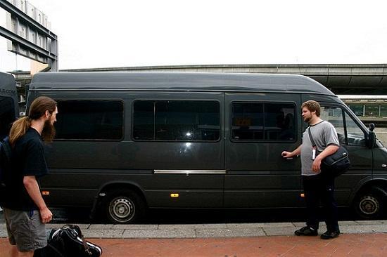 Duas pessoas próximas à porte de uma van escura