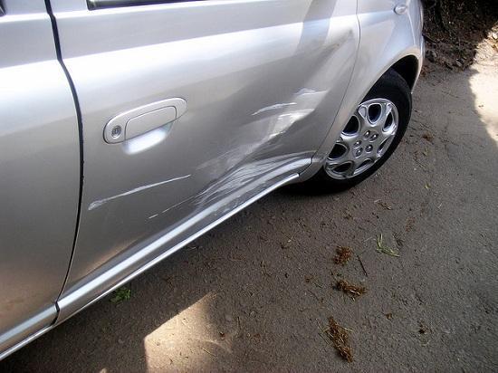 Carro prata com porta arranhada