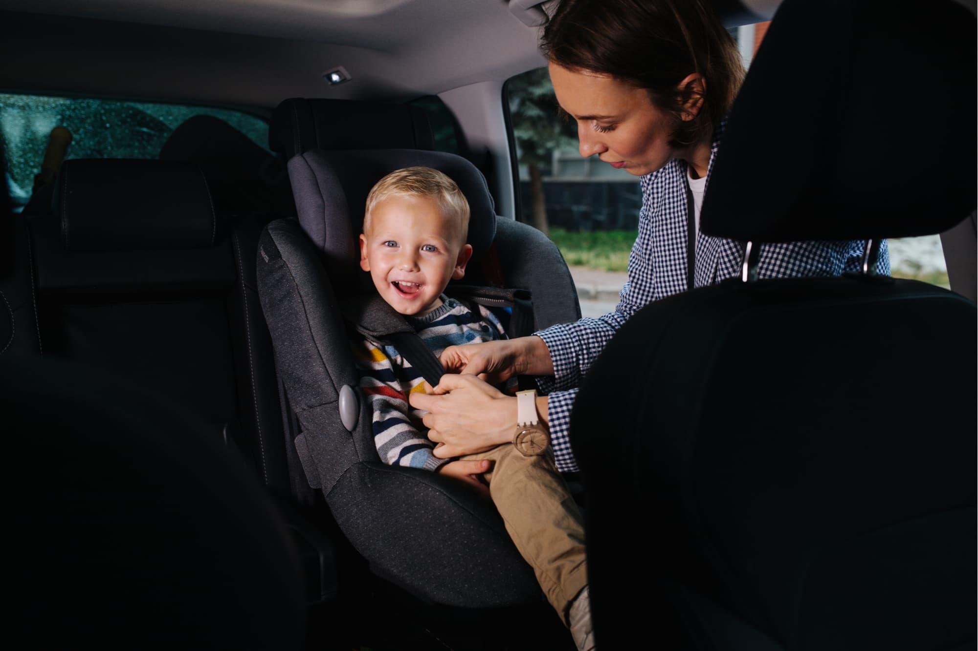 criança em cadeirinha de elevação no carro