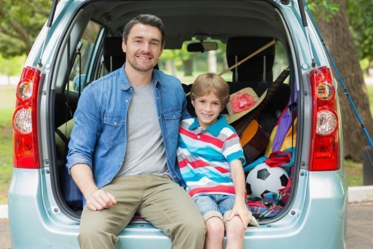 Pai e filho sentados no porta-malas de uma van