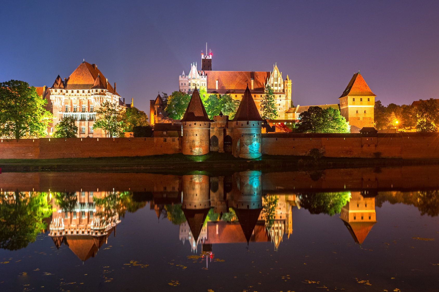 Malbork Castle from across the Nogat river at night. Poland. Europe.