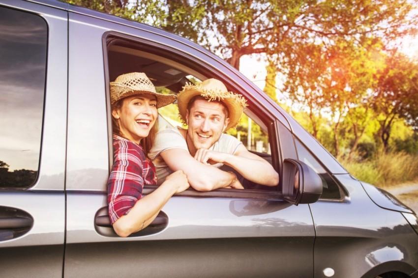 Casal em um carro com chapéus caipiras