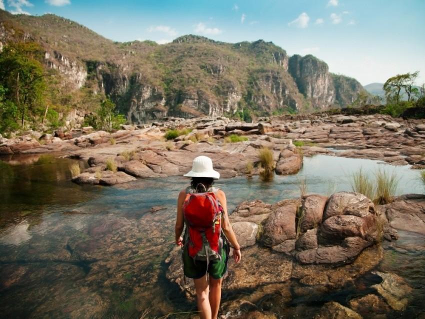 Turista fazendo trilha perto de um lago na Chapada dos Veadeiros