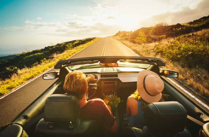 Casal viajando em um carro conversível