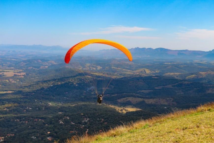 Pessoa saltando de parapente na Serra da Moeda em MG