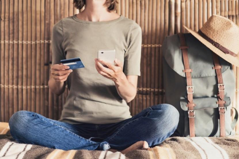Viajante com celular e cartão de crédito