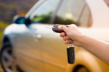 Mulher com chave na mão abrindo carro