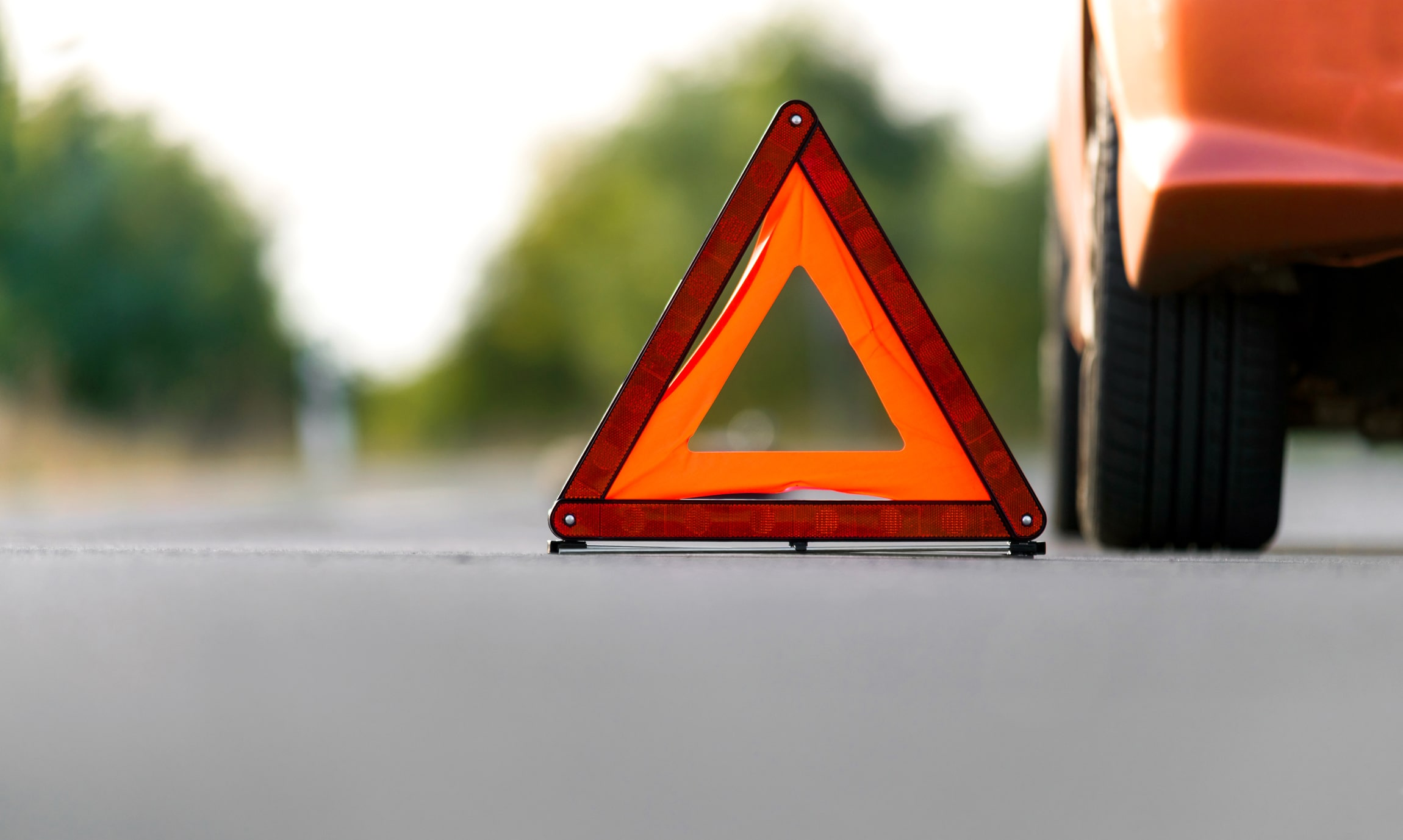 car parked on the side of the road with a red triangle