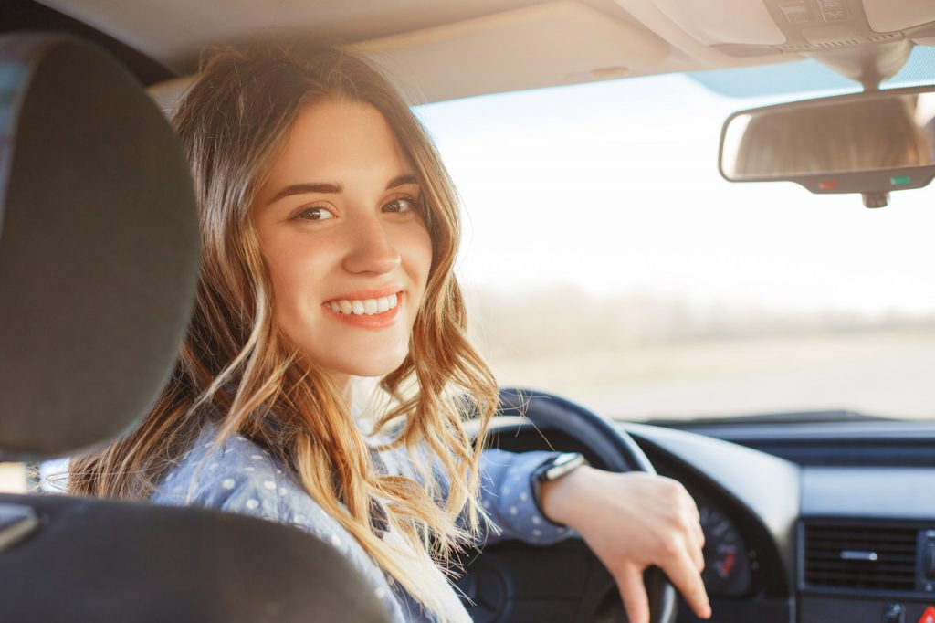Jovem mulher sentada no banco de motorista do carro, sorrindo e olhando para trás.