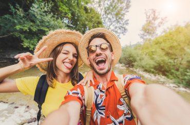 Um casal feliz, com roupas coloridas,tirando uma selfie em um lugar ao ar livre