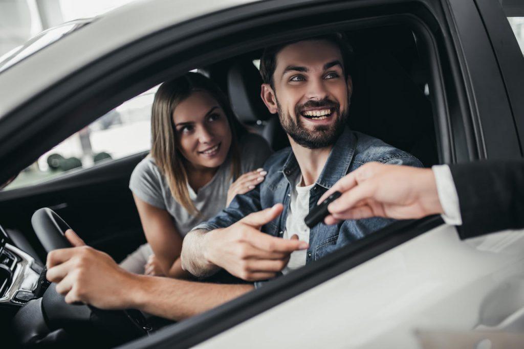 Casal dentro de um carro recebendo a chave