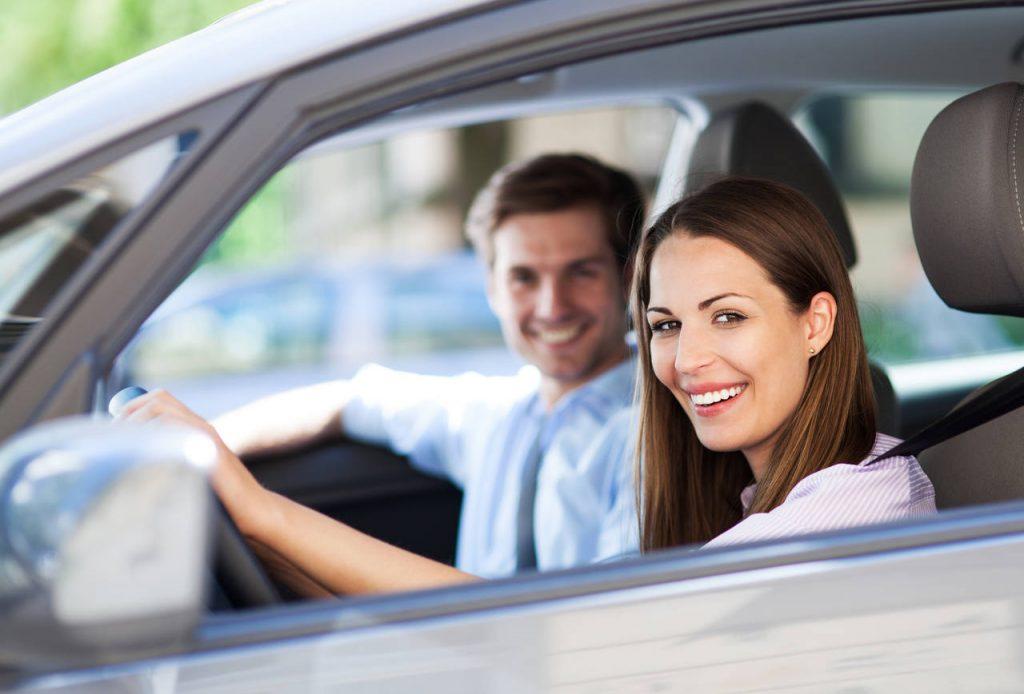 Casal sorrindo dentro de um carro