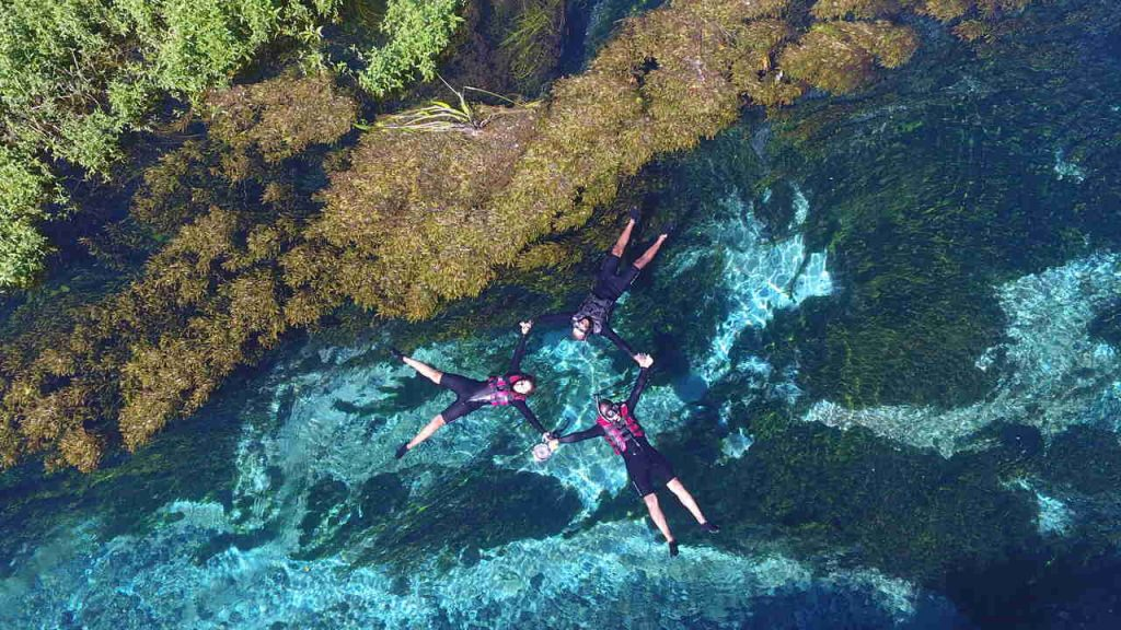Vista aérea do Rio Sucuri, em Bonito, com pessoas fazendo flutuação.