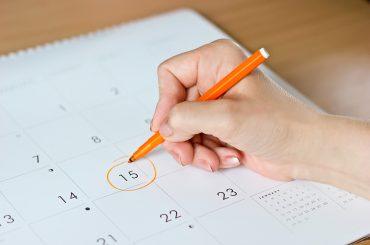 mão feminina circulando o número 15 em um calendário