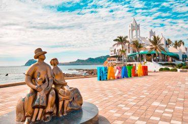 estatua de una familia y letras que dicen Mazatlán a la orilla de la playa. Al fondo el edificio Valentinos de mazatlan