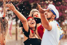 casal jogando confete no ar em uma festa de carnaval de rua
