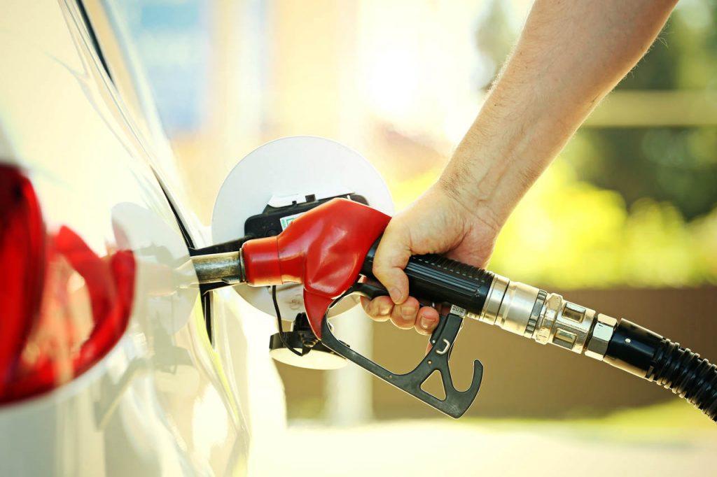 Mão masculina segurando bomba de combustível e abastecendo carro branco.