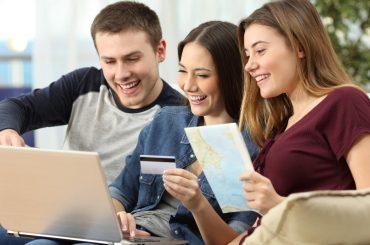 tres jovenes buscando ofertas de viaje en la computadora hot sale