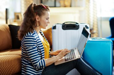 Mulher com um notebook no colo, mexendo no computador, com malas de viagem no fundo do ambiente