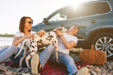 couple hugging a dog in front of a car
