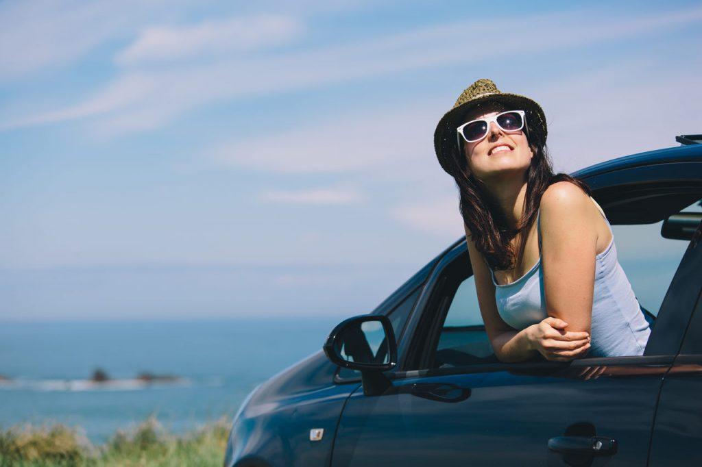 Mulher de chapéu e óculos escuros com o corpo para fora da janela do carro, sorrindo e apreciando a paisagem.