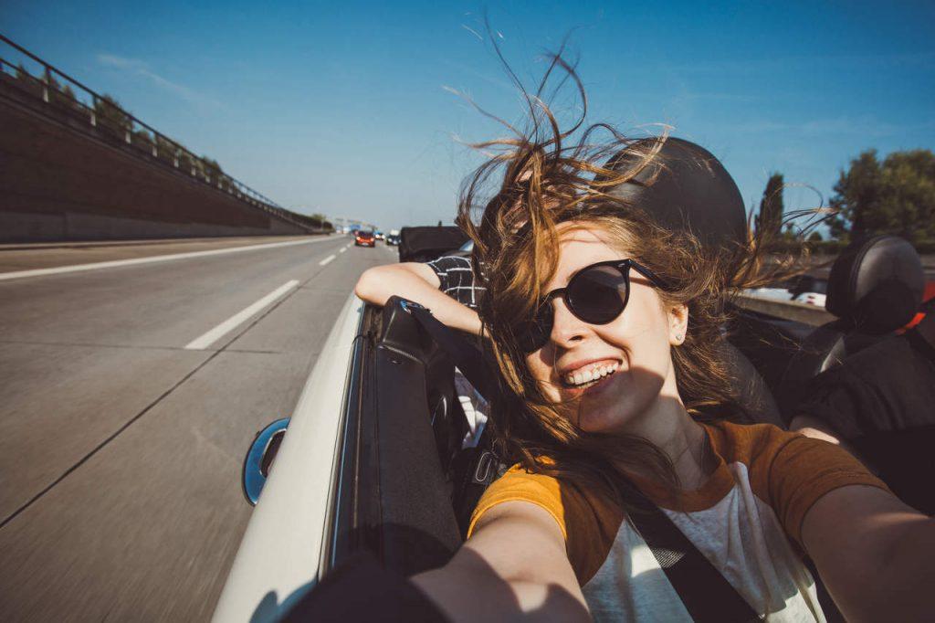 Jovem mulher com óculos escuros, sorrindo, em um carro conversível.