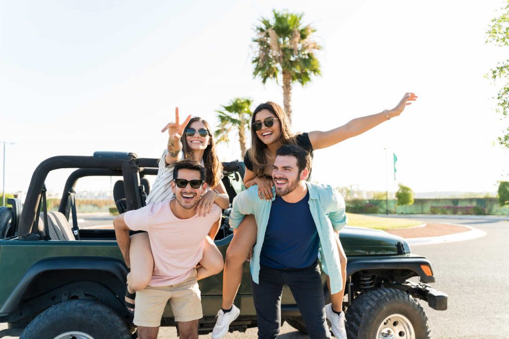 Dois casais felizes em frente a um carro jeep