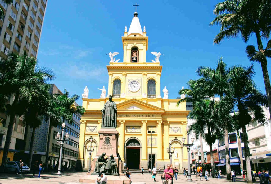 Fachada da Catedral Metropolitana de Campinas durante o dia, com pessoas andando e observando.