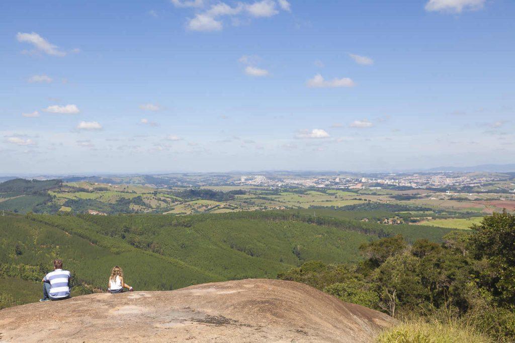 Um homem e uma menina sentados na parte mais alta do Pico das Cabras, apreciando a vista de Campinas.