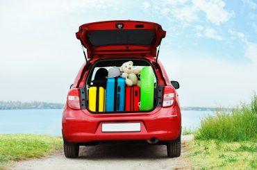 carro vermelho em uma praia com o porta malas aberto e cheio de malas coloridas