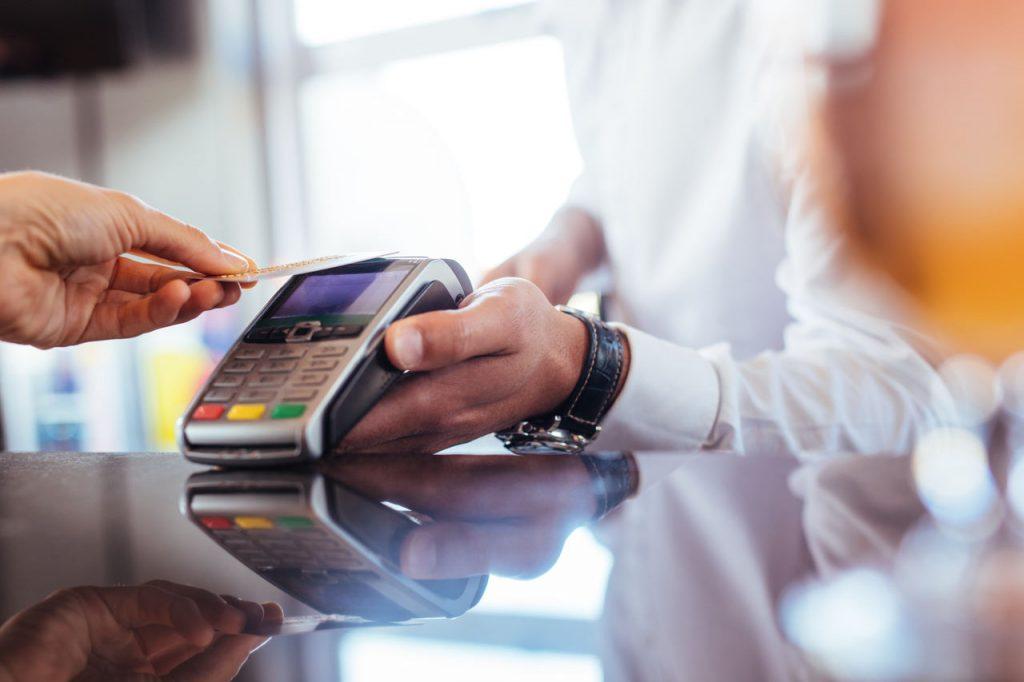 Imagem focada em uma mão masculina segurando um cartão para passar em uma máquina de cartão de crédito