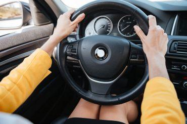 mãos femininas segurando o volante de um carro