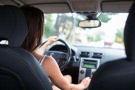 mulher jovem, com cabelo castanho, dirigindo um carro