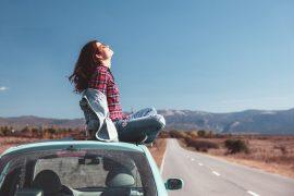 mulher sentada no teto do carro curtindo a paisagem da estrada