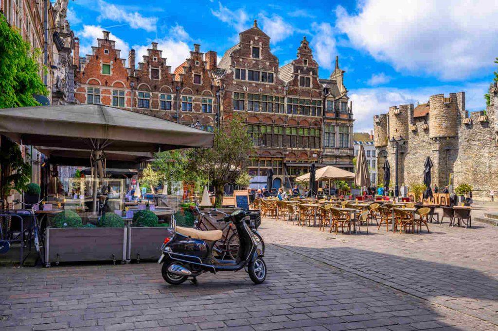 Antiga praça em Gent, Belgica, com mesas ao ar livre e uma moto antiga estacionada.