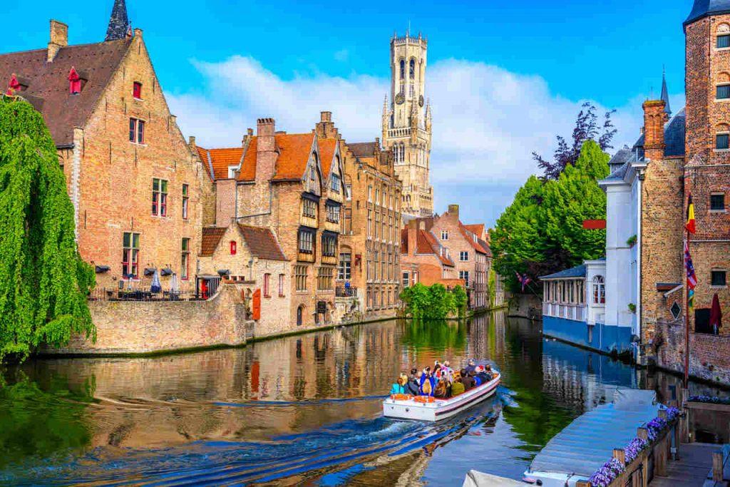 Vista diurna dos canais de Bruges, com um barco de turistas navegando, cercado por construções antigas.