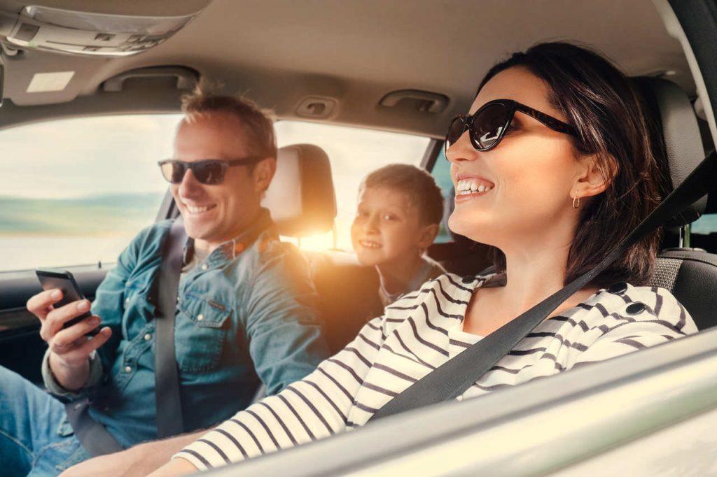 Familia no carro, onde a mulher está dirigindo, o marido está no banco do carona e o filho no banco traseiro.