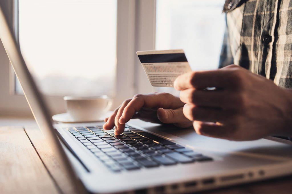 Mão masculina segurando um cartão de crédito em frente ao notebook prata