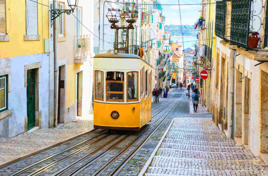 Bonde amarelo circulando pelas ruas antigas de Lisboa
