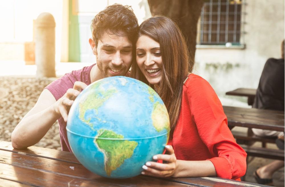 casal observando globo terrestre