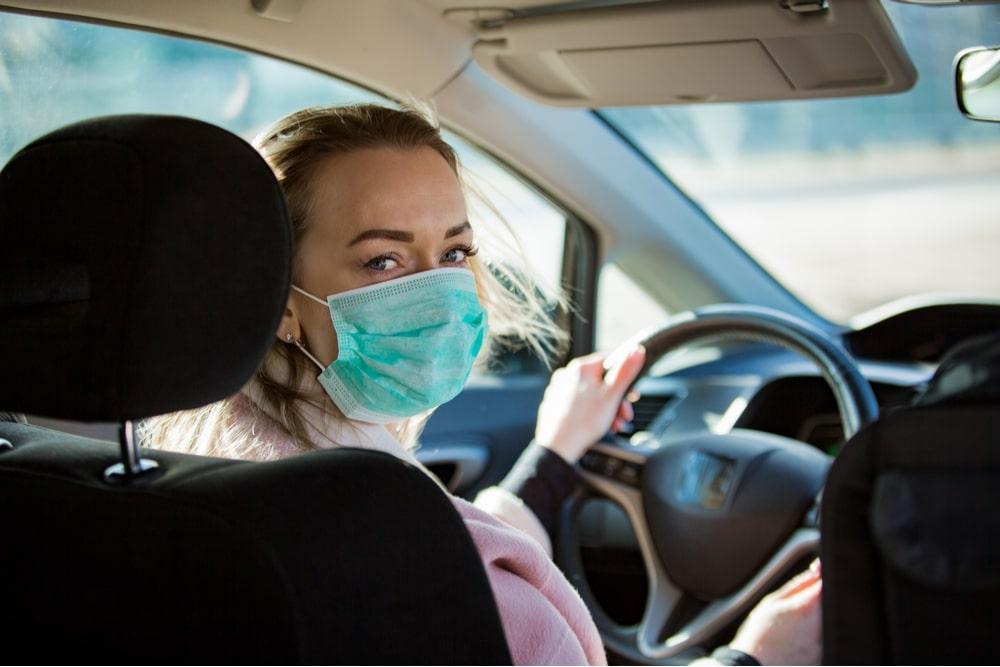 mulher dirigindo carro de mascara