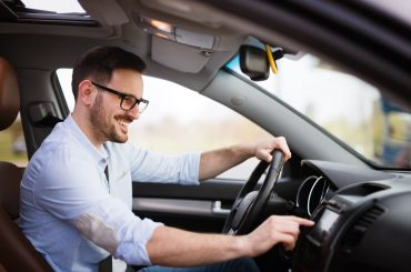 man smiling driving a car