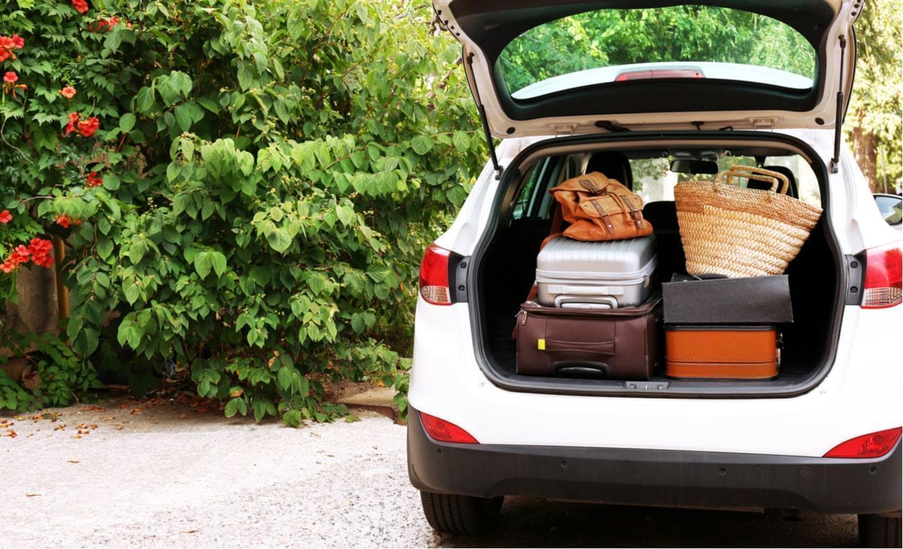 carro branco com porta malas aberto com bagagens