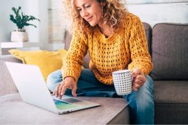 woman in yellow sweater with a mug in hand using a laptop