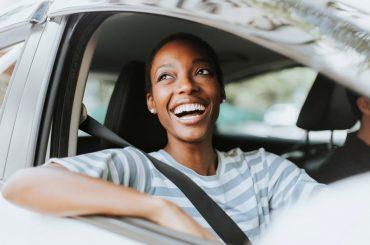 mulher sorrindo dentro de um carro