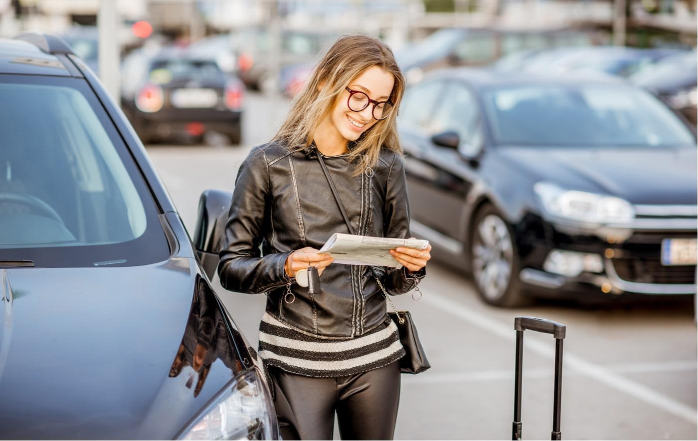 mulher com documento de aluguel de carro na mão