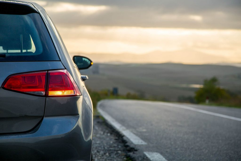 carro parado em beira de estrada dando sinal