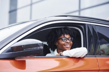 woman inside driver's side of an orange car