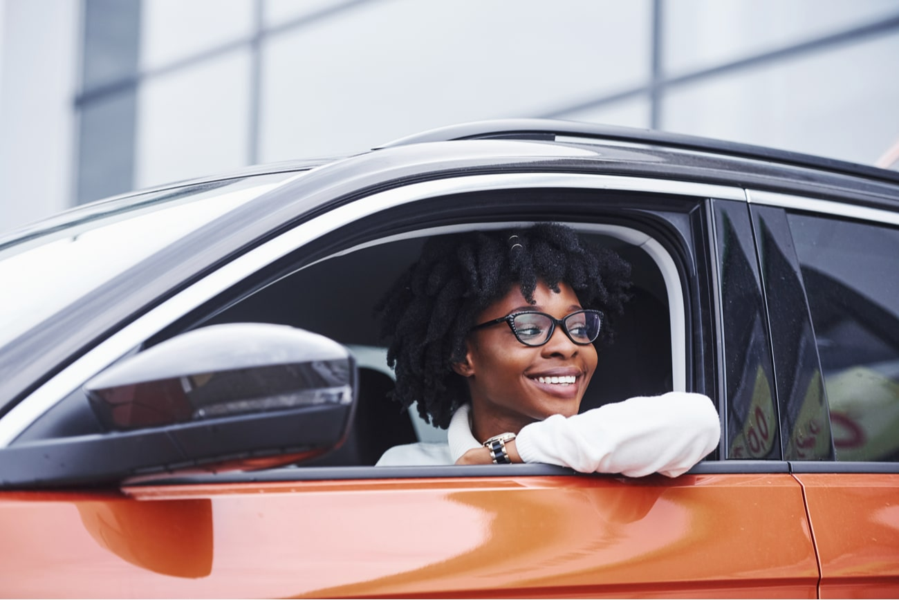woman inside driver's side of an orange car